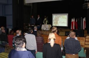 Uroczystość w MDK w Przedborzu - zebrani śpiewają Mazurka Dąbrowskiego; na scenie, za stolikiem, od lewej: wiceprezes TMP i radny w Przedborzu Paweł Zięba, inicjator uroczystości i prelegent Adam W. Gorycki z Kielc.